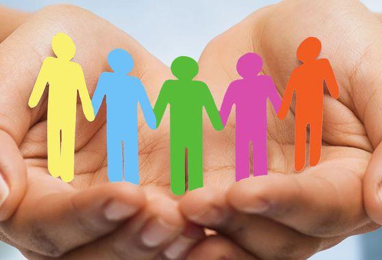 deux mains ouvertes vers l'extérieur tiennent une guirlande colorée de bonhommes en papier qui se donnent la main