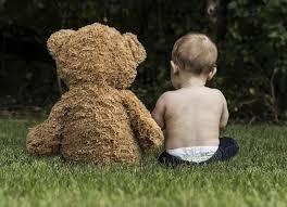 bebe position assise a côté d'un ours en peluche