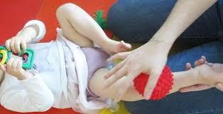 adulte qui masse un enfant en couche avec une balle