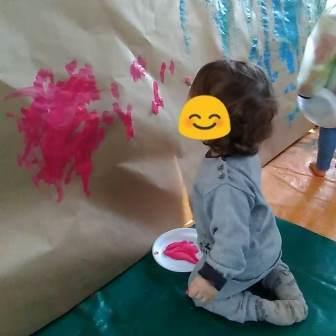 enfants à genoux qui peind sur du papier craft