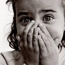 enfant qui a peur qui se cacahe le visage avec les deux mains