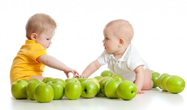 deux enfants se font faces avec des pommes vertes devant eux